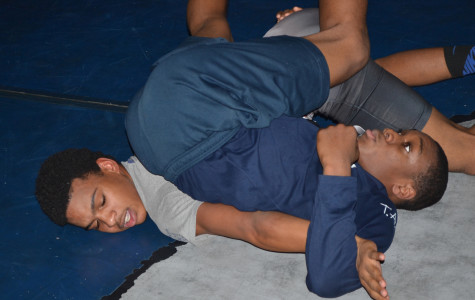 Pinned: Senior Keith Lee practices his arm drag moves on senior Davion Williams in preparation for State competition this year. Last year he made it to states but did not place. He aims this year to accomplish what he did not get done last year.