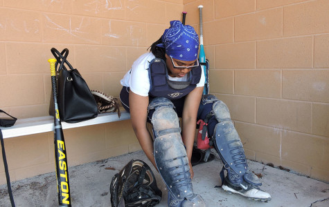 Catch me: Softball catcher Adriana Echols suits up between innings during a home game.