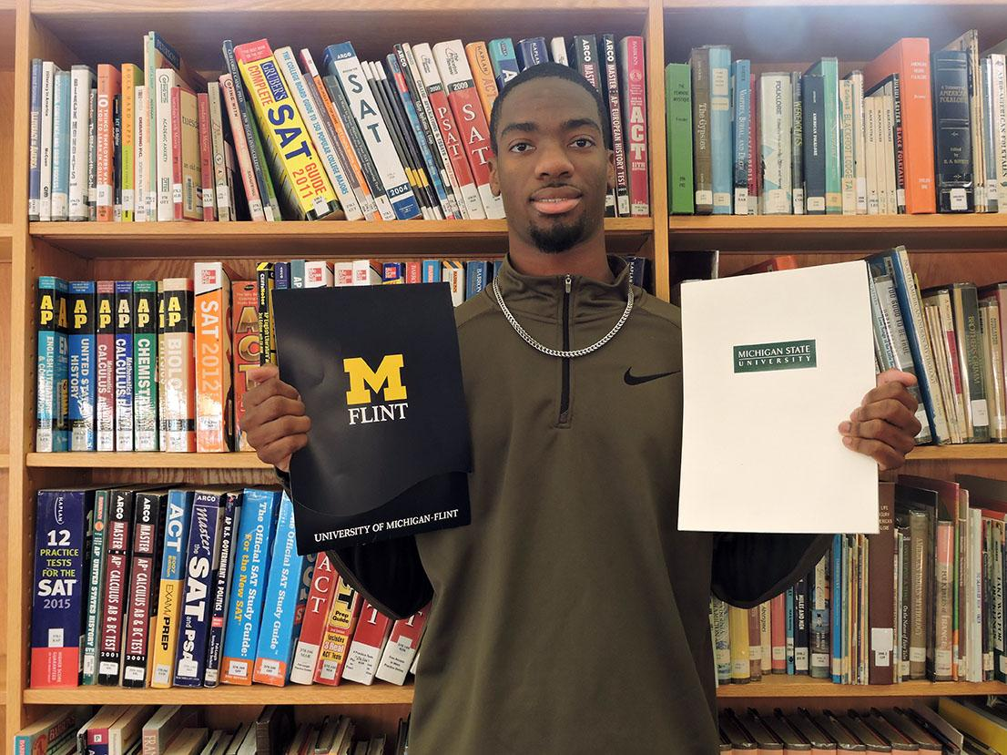 Accepted: Senior Brandon Smith proudly displays his acceptance materials from the University of Michigan-Flint and from Michigan State University.