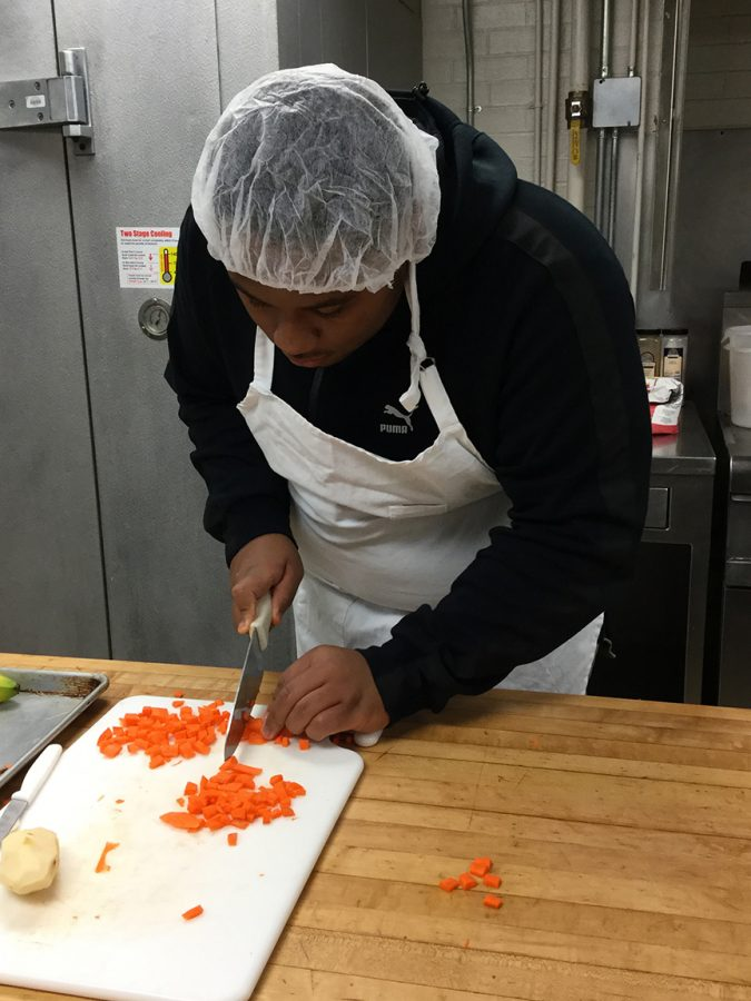 Senior Marcus Rutledge dices carrots for his culinary arts class. Students are required to wear hair nets to keep hair out of the food.