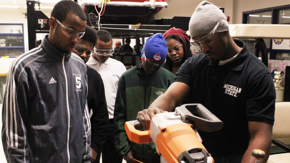 Robotics team members get a lesson in using a miter saw from Southfield High alumnus Lee Johnson, Jr. (in the hat). Pictured with Lee are (from left) senior Ryan Bailey and Jalen Smith, and sophomores William Dixon, Tovan Heyden and Rachel Walker.