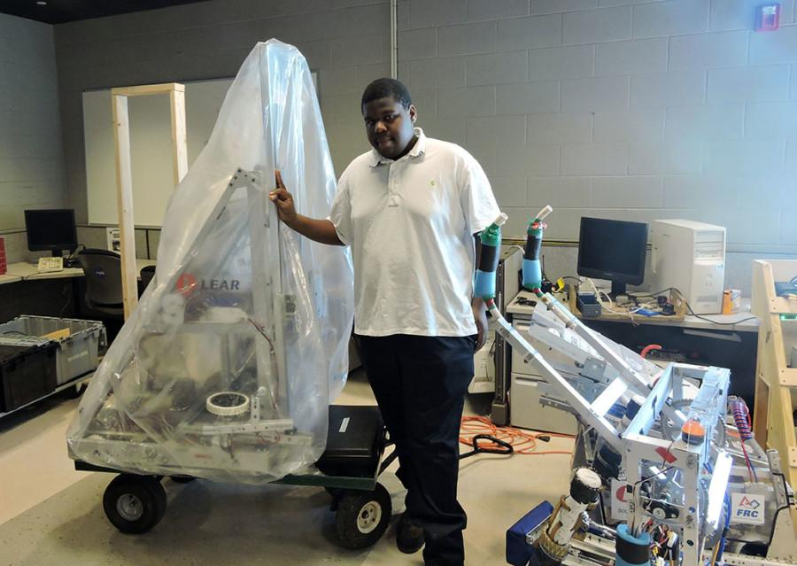 Under wraps: Senior Kenneth Warrior stands beside Southfield Highs robot that is scheduled to compete against 39 other robots. It is wrapped for secrecy.