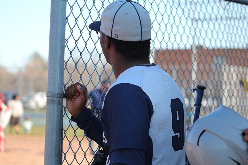 Senior William Flood watches his teammates play Oak Park High School.